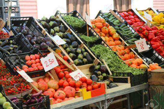 fruit and vegetable stand with basket full of seasonal fruits in